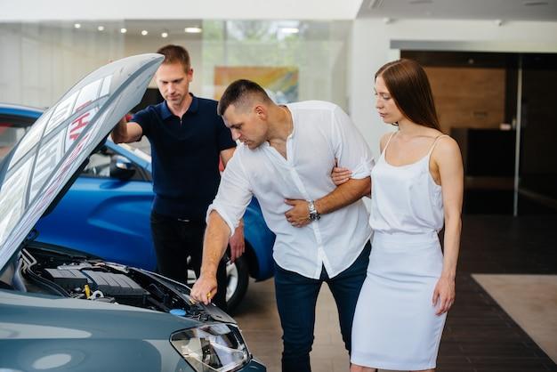 Een jong stel kiest bij de dealer een nieuwe auto en overlegt met een vertegenwoordiger van de dealer. tweedehands auto's te koop. droomvervulling.