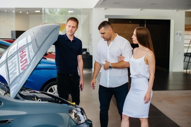 Een jong stel kiest een nieuwe auto bij de dealer en overlegt met een vertegenwoordiger van de dealer. tweedehands auto's te koop. droomvervulling.
