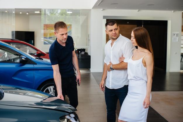 Een jong stel kiest een nieuwe auto bij de dealer en overlegt met een vertegenwoordiger van de dealer.