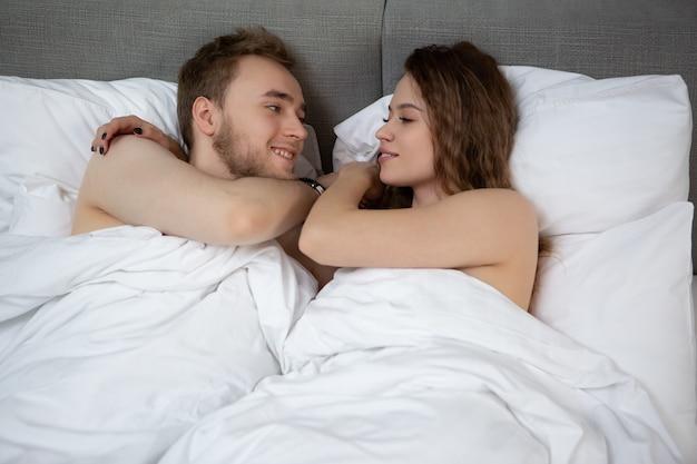 Een jong stel knuffelt thuis in een goed humeur op hun bed