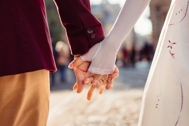 Een jong stel loopt door de stad en houdt elkaars hand vast