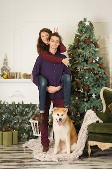 Een jong stel met een hond die rond een kerstboom voor de gek houdt. gelukkig nieuwjaar en vrolijk kerstfeest