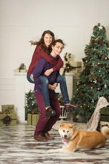 Een jong stel met een hond die rond een kerstboom voor de gek houdt