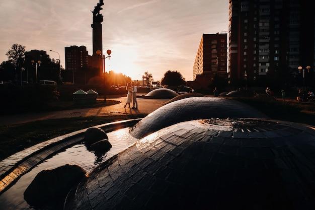 Een jong stel omhelst in de stad bij een prachtige zonsondergang, stedelijke stijl.
