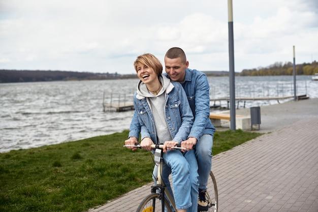 Een jong stel op een fiets rijdt langs het meer.