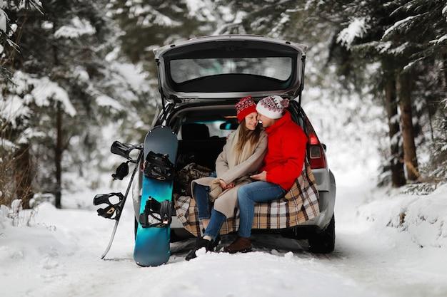 Een jong stel snowboardersman en -vrouw zitten in de kofferbak van zijn auto in een knuffel