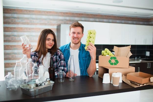 Een jong stel sorteert afval in de keuken. de jonge man en de vrouw sorteren recycleerbare voorwerpen in de keuken. er is karton, papier, ijzer, plastic en glas en andere materialen die gerecycled kunnen worden.