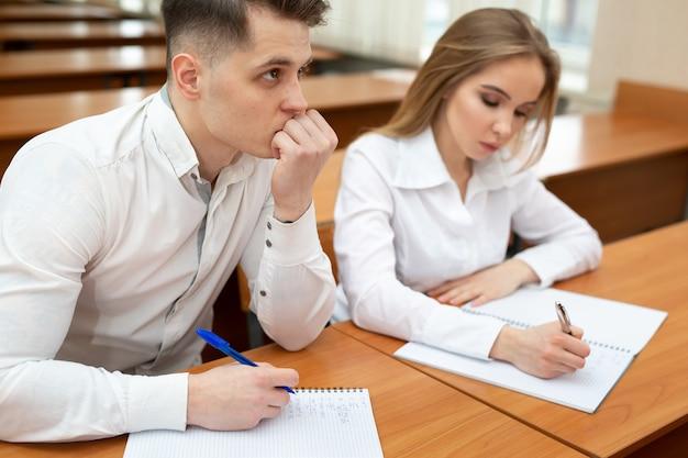 Een jong stel studenten, een jongen en een meisje, zitten aan een bureau bij een lezing en houden elkaars hand vast