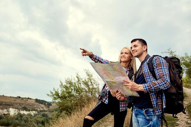 Een jong stel toeristen met een kaart in een wandeling in de natuur.