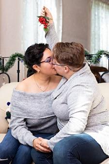 Een jong stel van twee vrouwen die zichzelf een kus geven in een woonkamer die is ingericht voor kerstmis