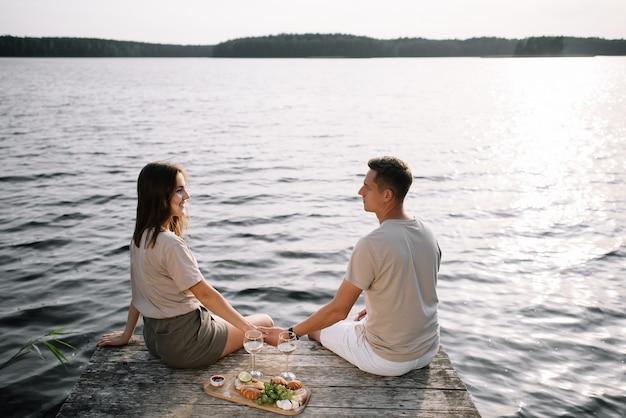 Een jong stel zit op de pier bij het meer