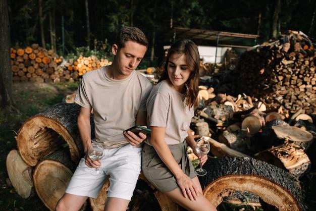 Een jong stel zit op gekapte bomen in het bos en kijkt naar hun telefoon