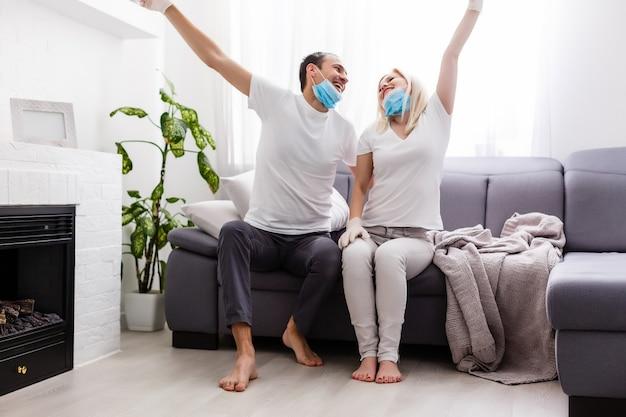 Een jong stel zit thuis in zelfquarantaine. man en vrouw hebben het coronavirus in beschermende maskers in quarantaine geplaatst. nieuwe realiteit. normaal leven in afzondering. lees samen een boek. italië europa covid-19