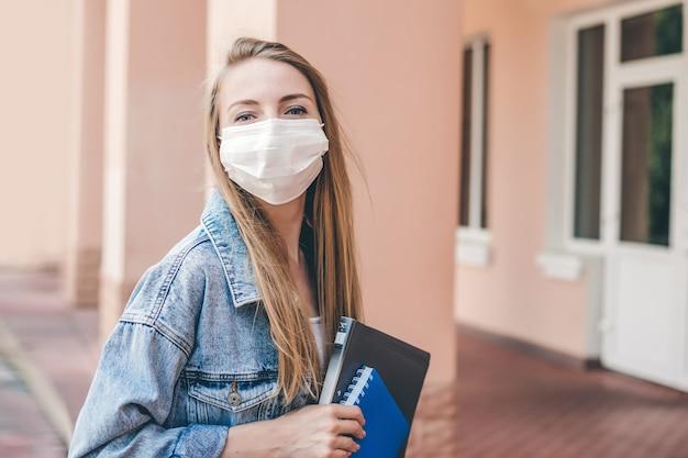 Een jong studentenmeisje dat een medisch beschermend gezichtsmasker draagt, komt het universiteitsgebouw binnen en houdt een pak notitieboekjes en schriften in haar handen en kijkt naar de camera