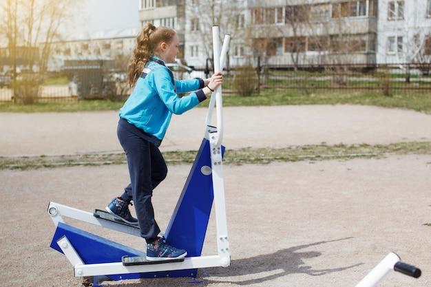 Een jong tienermeisje in een blauwe jas, met lang haar dat lacht en buitenoefeningen doet op straatsimulators. sport, fitness, straattrainingsconcept.