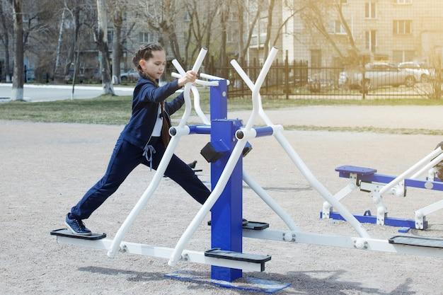 Een jong tienermeisje in een donkerblauw sportpak, met lang haar dat lacht en oefeningen doet op straat op de simulators. sport, fitness, straattrainingsconcept.