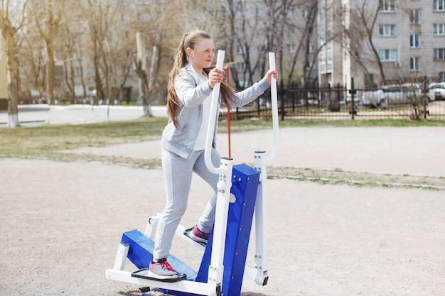Een jong tienermeisje in een grijs sportpak, met lang haar dat lacht en buitenoefeningen doet op straatsporters. sport, fitness, straattrainingsconcept.