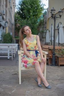 Een jong tienermeisje in een jurk zit op een terras in de straat