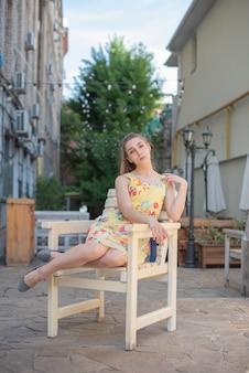 Een jong tienermeisje in een jurk zittend in de straat