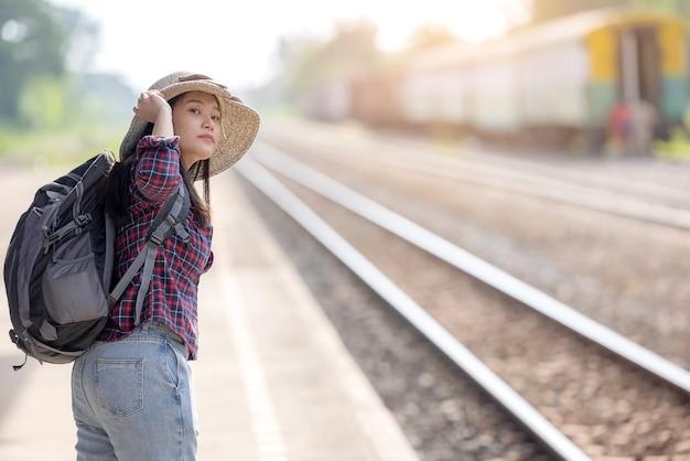 Een jong toeristenmeisje met rugzak wacht op de trein op het treinstation voor reizen en reizen and