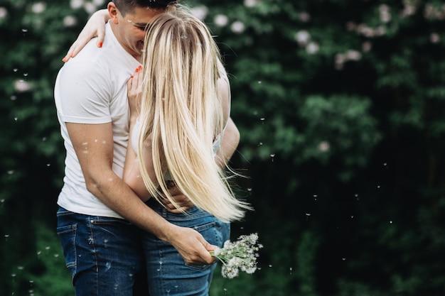 Een jong verliefd paar zoenen in het park voor een bloeiende struik