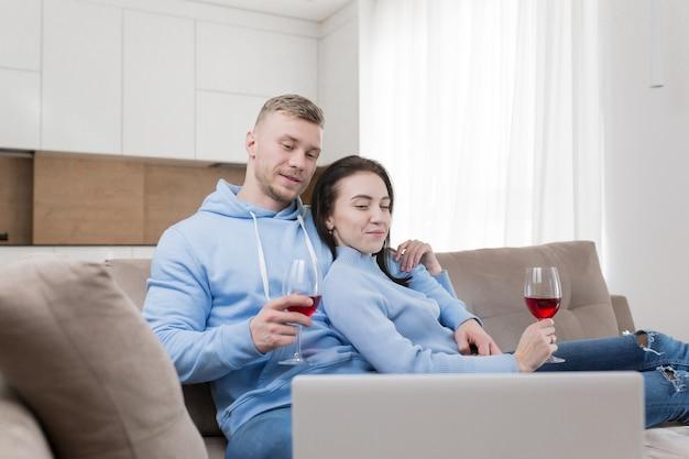 Een jong verliefd stel, een man en een vrouw die op de bank ontspannen en naar een laptop kijken