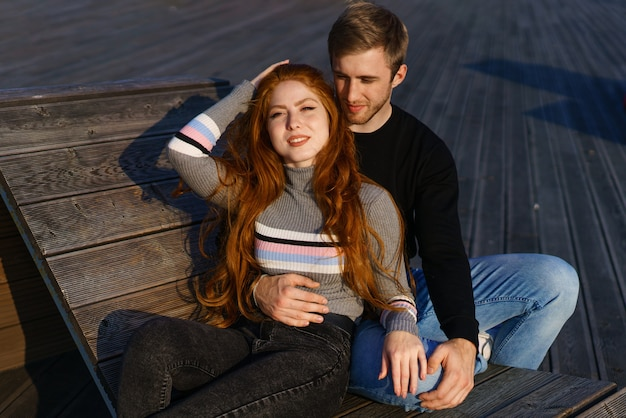 Een jong verliefd stel een man en een vrouw omhelzen op een bankje in het recreatiegebied een mooie rode ha...