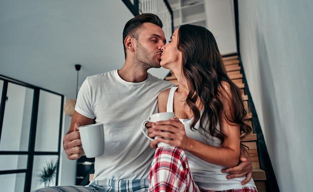 Een jong verliefd stel in pyjama zit op de trappen van hun huis en drinkt 's ochtends koffie.