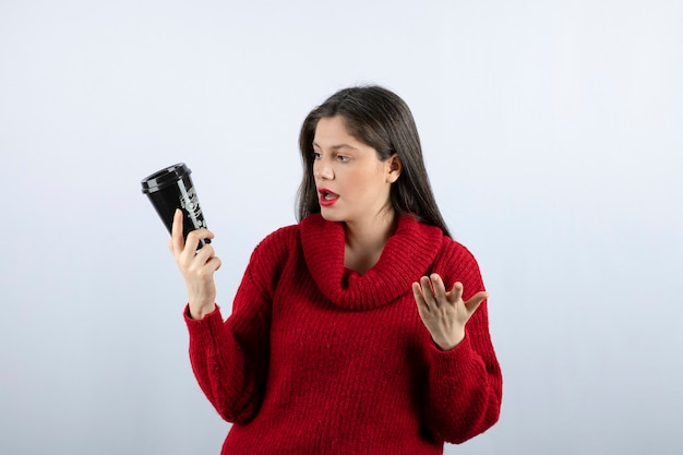 Een jong vrouwenmodel in een rode trui die naar een kopje koffie kijkt