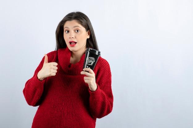 Een jong vrouwenmodel in rode trui met een kopje koffie met een duim omhoog