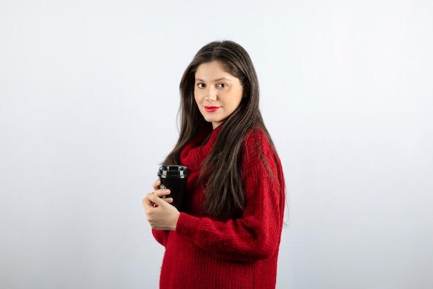 Een jong vrouwenmodel in rode trui met een kopje koffie