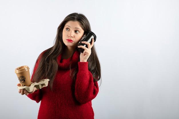 Een jong vrouwenmodel in rode trui met twee kopjes koffie