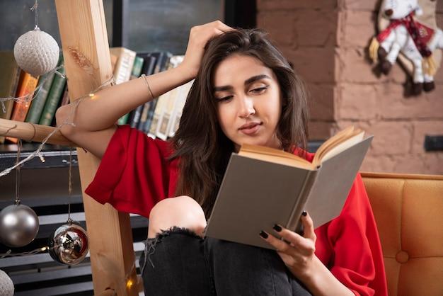 Een jong vrouwenmodel zit en leest een boek.
