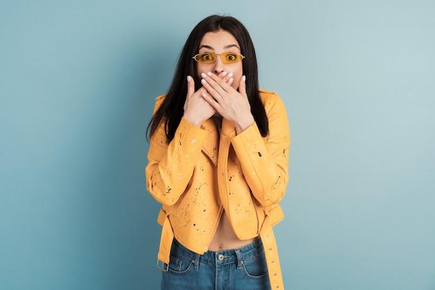 Een jong vrouwtje in een oranje jasje op een blauwe muur bedekt haar mond met beide handen