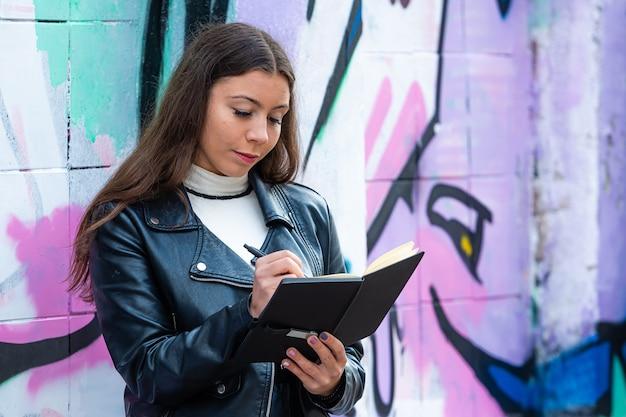 Een jong vrouwtje leunt tegen een met graffiti bespoten muur en maakt aantekeningen in een zwart notitieboekje