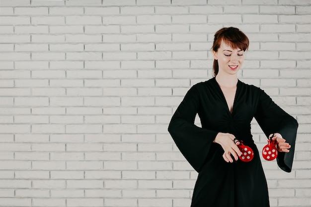 Een jonge aantrekkelijke vrouw in zwarte jurk, dansen met rode castagnetten, glimlachen, witte muur achtergrond