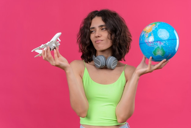 Een jonge aantrekkelijke vrouw met kort haar in groene crop top in koptelefoon met globe en kijken naar speelgoed vliegtuig