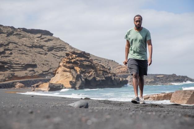 Een jonge afrikaanse jongen loopt in de zomer op het strand van lanzarote en denkt na