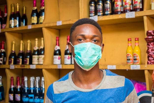Een jonge afrikaanse man in een supermarkt die een gezichtsmasker draagt om een uitbraak te voorkomen