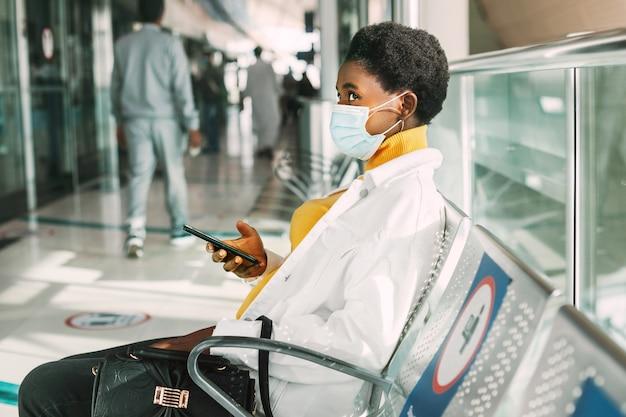 Een jonge afrikaanse vrouw met een beschermend masker zit in een stoel in de wachtkamer en leest e-mails op haar telefoon. sociale afstand, pandemie.