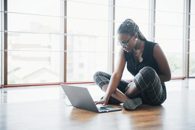 Een jonge afro-amerikaanse vrouw is blij met een laptopcomputer.