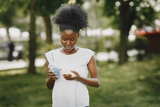 Een jonge afro-amerikaanse vrouw kijkt naar een telefoon in het park