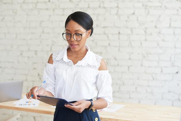 Een jonge afro-amerikaanse vrouw staat in een stijlvol kantoor en kijkt in een notitieboekje