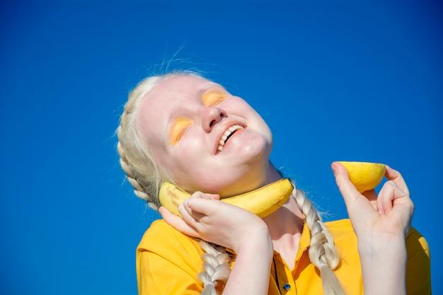 Een jonge albinovrouw houdt een banaan tegen haar oor als een telefoon tegen de blauwe lucht