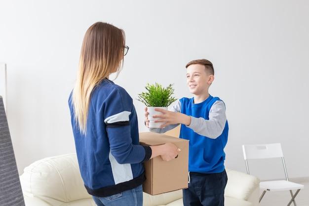 Een jonge alleenstaande moeder en een speels zoontje houden een doos met spullen en een bloem in een pot in de woonkamer van een nieuw appartement. housewarming en nieuw woonconcept.