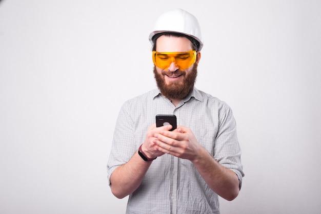 Een jonge architect sms't blij op zijn telefoon met een beschermende bril en een hemlet bij een witte muur