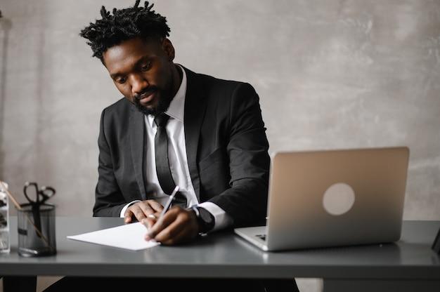 Een jonge aspirant-afrikaans-amerikaanse investeerder werkt op een computer
