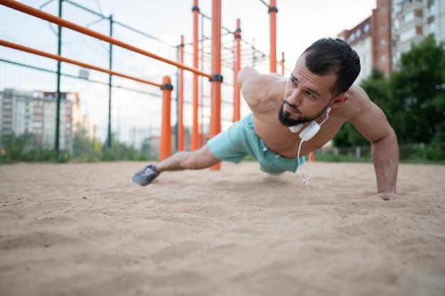 Een jonge atleet doet in de zomer aan één hand push-ups op het zand. sport, fitness, straattraining concept