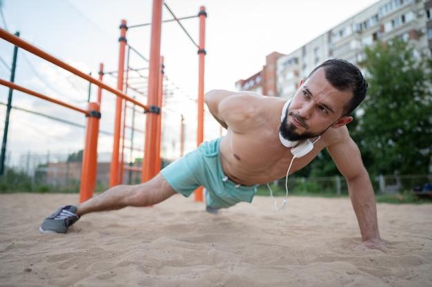 Een jonge atleet doet push-ups aan de ene kant op het zand in de zomer. sport, fitness, straattrainingsconcept