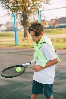 Een jonge atleet houdt een tennisracket met een bal erop. tennisser warmt op voor de training